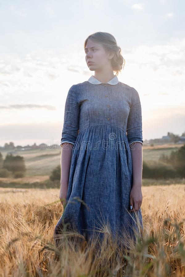 Ragazza in vestito blu con capelli raccolti che posano con i suoi occhi chiusi nel campo ad alba Alba nebbiosa nel fondo immagine stock libera da diritti