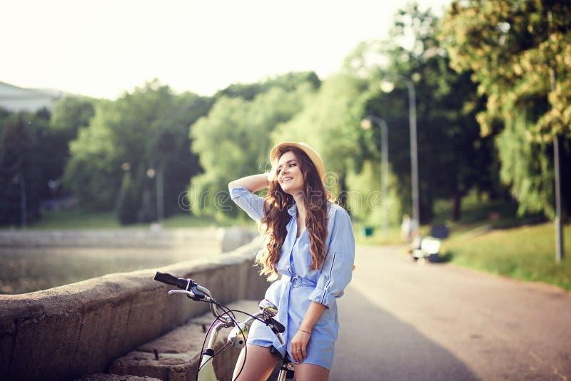 Ragazza in vestito che guida una bicicletta attraverso la città fotografie stock libere da diritti