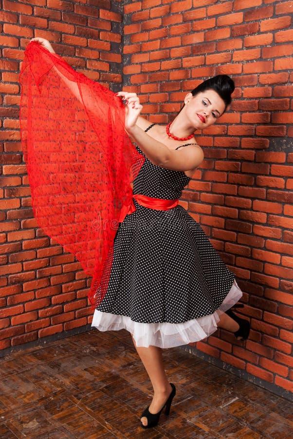 Ragazza in vestito d'annata che balla vicino al muro di mattoni fotografia stock libera da diritti