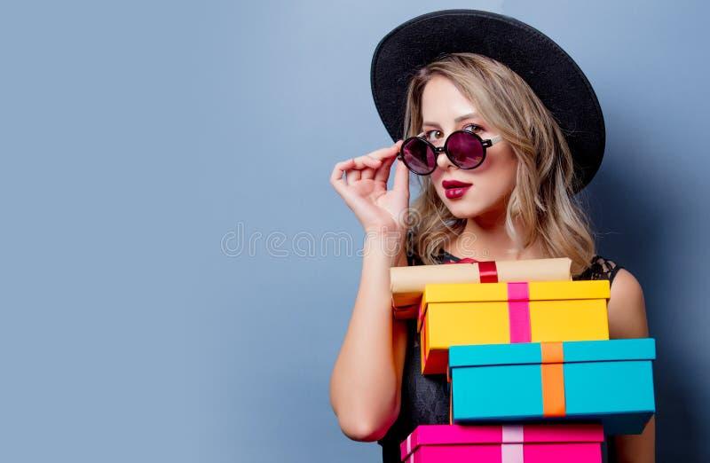 Ragazza in vestito e cappello neri con i contenitori di regalo immagine stock