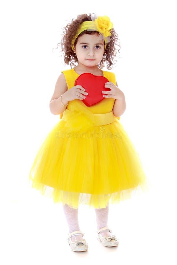 Ragazza in vestito giallo che tiene cuore rosso immagine stock