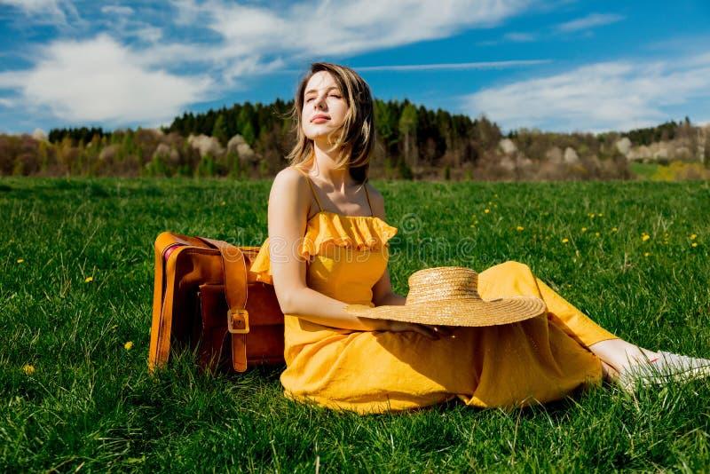 Ragazza in vestito giallo e valigia che si siedono sul prato della montagna con i denti di leone immagine stock libera da diritti