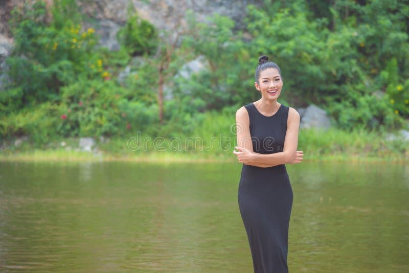 Ragazza in vestito nero che sorride vicino dal fiume immagini stock libere da diritti