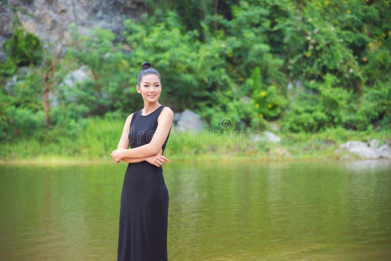 Ragazza in vestito nero che sorride vicino dal fiume immagini stock