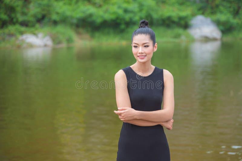 Ragazza in vestito nero che sorride vicino dal fiume fotografie stock