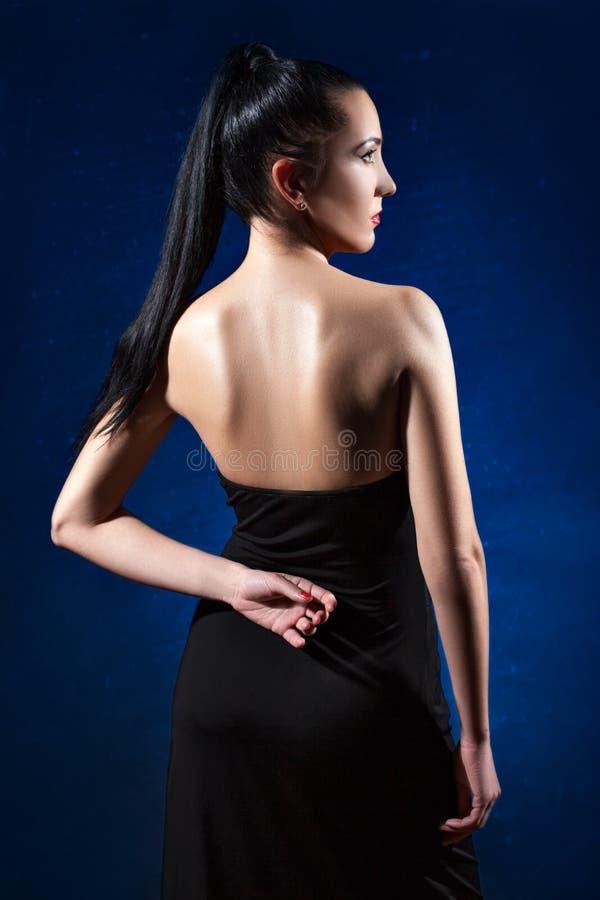 Ragazza in vestito nero su un fondo blu che posa indietro immagini stock