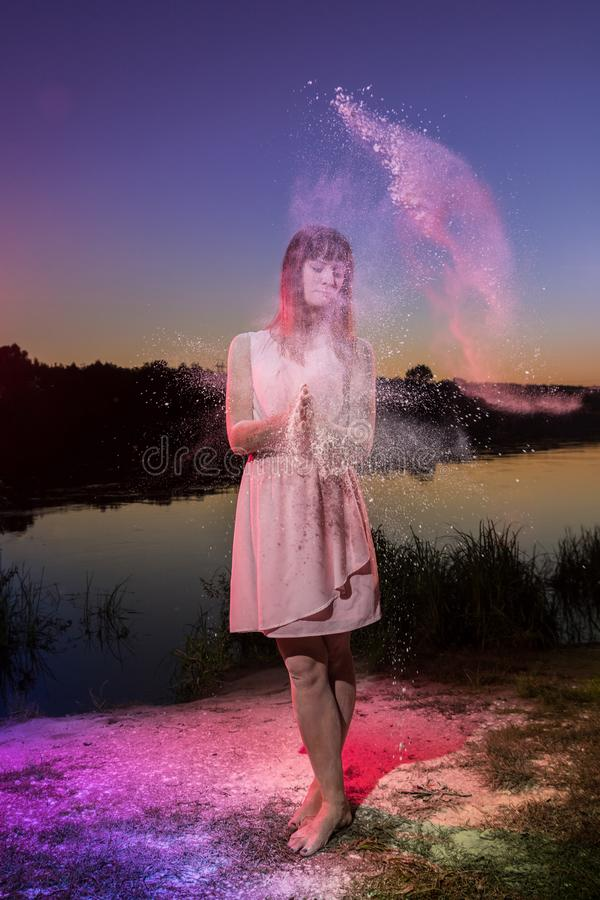 Ragazza in vestito rosa sulla spiaggia del fiume durante il tramonto e la nuvola di farina bianca intorno lei immagine stock