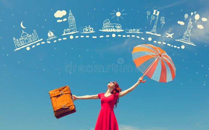 Ragazza in vestito rosso con la valigia e l'ombrello fotografia stock libera da diritti