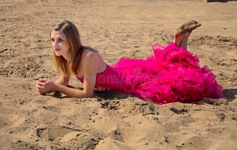 Ragazza in vestito rosso da promenade che mette su spiaggia immagini stock libere da diritti