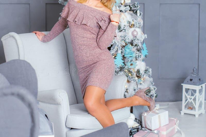 Ragazza vicino all'albero di Natale in un colore tricottato del cappuccino del vestito fotografia stock libera da diritti