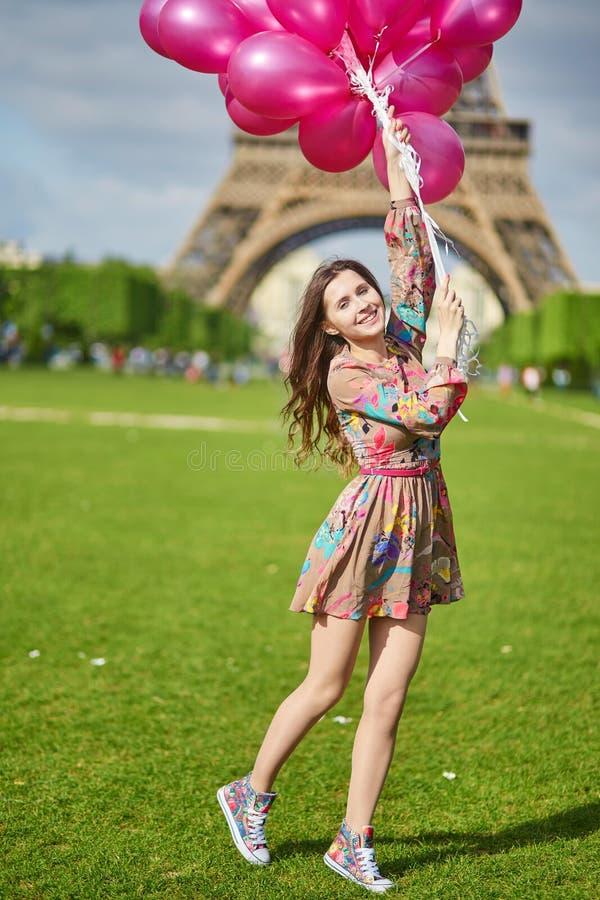 Ragazza vicino alla torre Eiffel a Parigi con il mazzo enorme di palloni rosa fotografia stock
