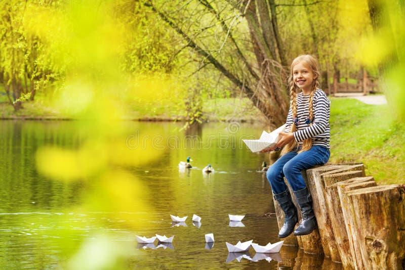 Ragazza vicino allo stagno che gioca con le barche di carta in foresta immagine stock libera da diritti