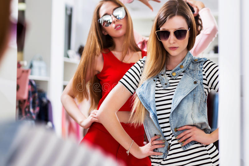 Ragazze affascinanti che provano sugli occhiali da sole che posano davanti allo specchio nel boutique di modo fotografia stock libera da diritti