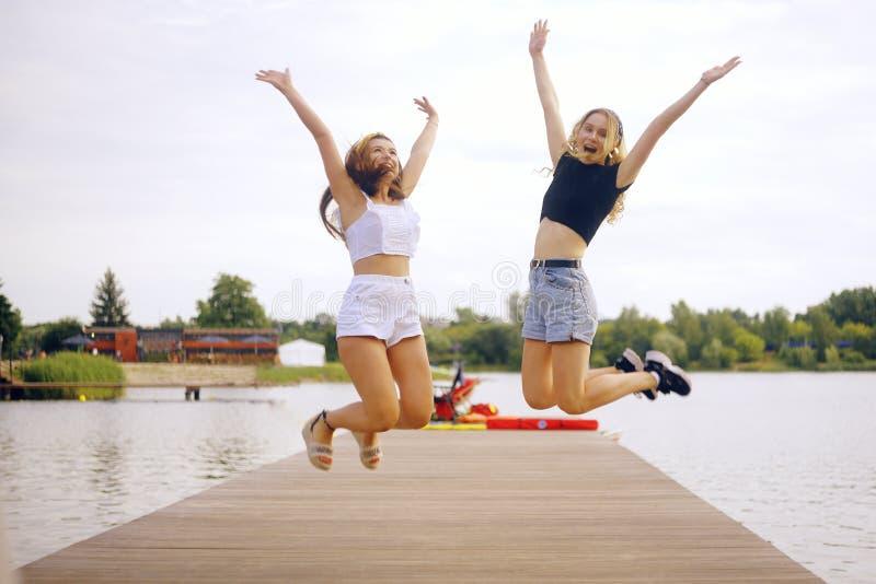 Ragazze al molo vicino al fiume, al lago, alla spiaggia Le ragazze saltano, alzano la mano, felicità, gioia vacanze estive, immagine stock libera da diritti