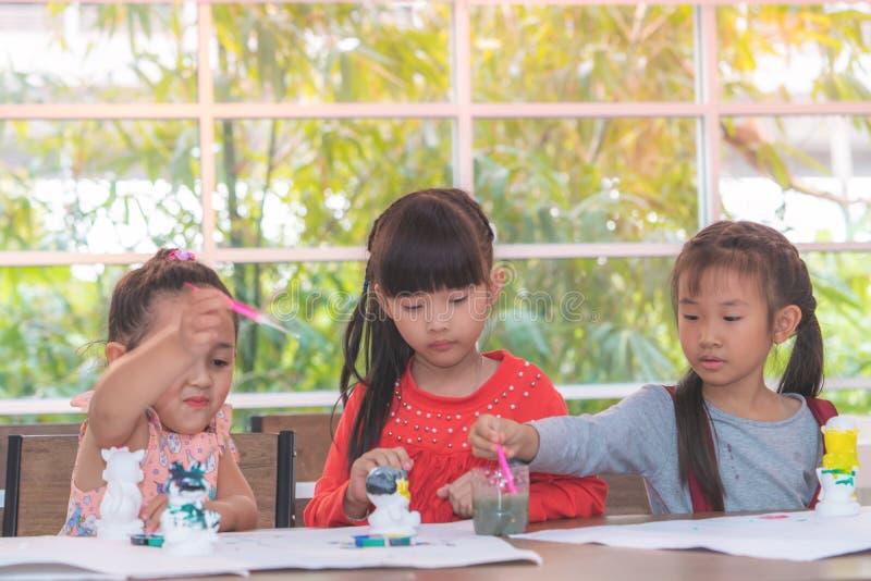 Ragazze asiatiche che dipingono le bambole immagini stock