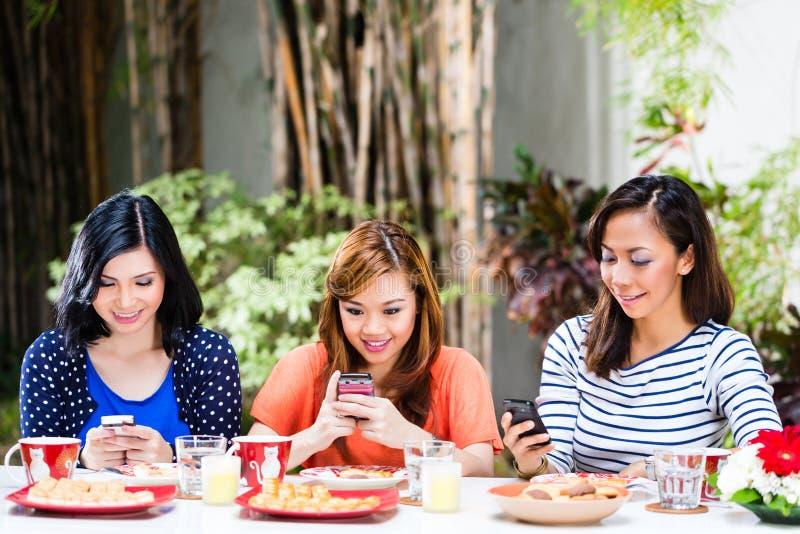 Ragazze asiatiche che per mezzo dei loro telefoni cellulari immagine stock