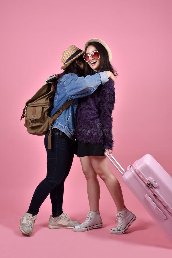 Ragazze asiatiche sorridenti del viaggiatore che si abbracciano all'aeroporto immagini stock libere da diritti
