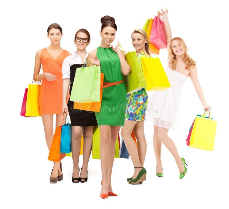 Ragazze attraenti che tengono i sacchetti della spesa di colore fotografia stock libera da diritti
