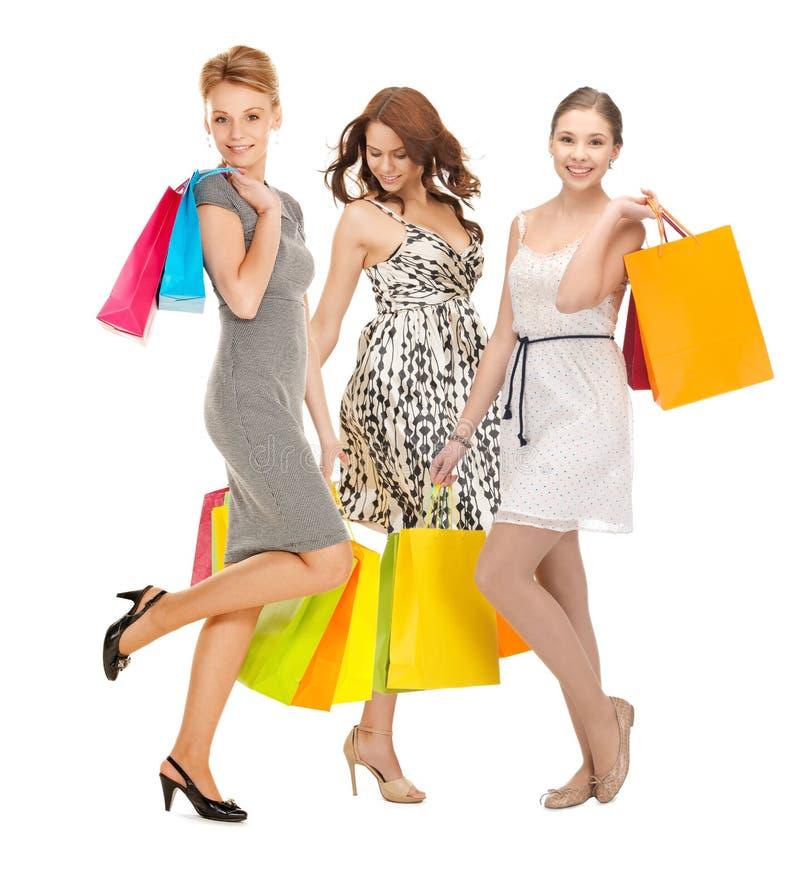 Ragazze attraenti che tengono i sacchetti della spesa di colore immagini stock libere da diritti