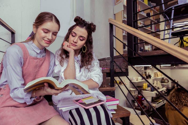 Ragazze calme e pacifiche che si siedono spalla a spalla e libro di lettura immagine stock