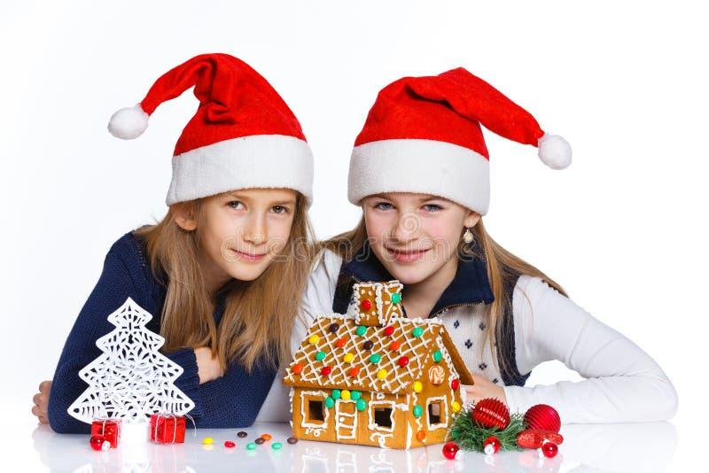 Ragazze in cappello di Santa con la casa di pan di zenzero fotografia stock libera da diritti