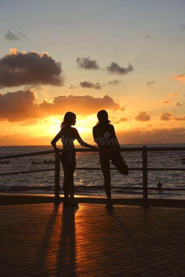 Ragazze che allungano al tramonto immagini stock