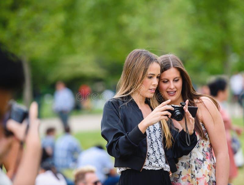 Ragazze che ammirano le fotografie che hanno preso sulla camma mirorrless immagine stock