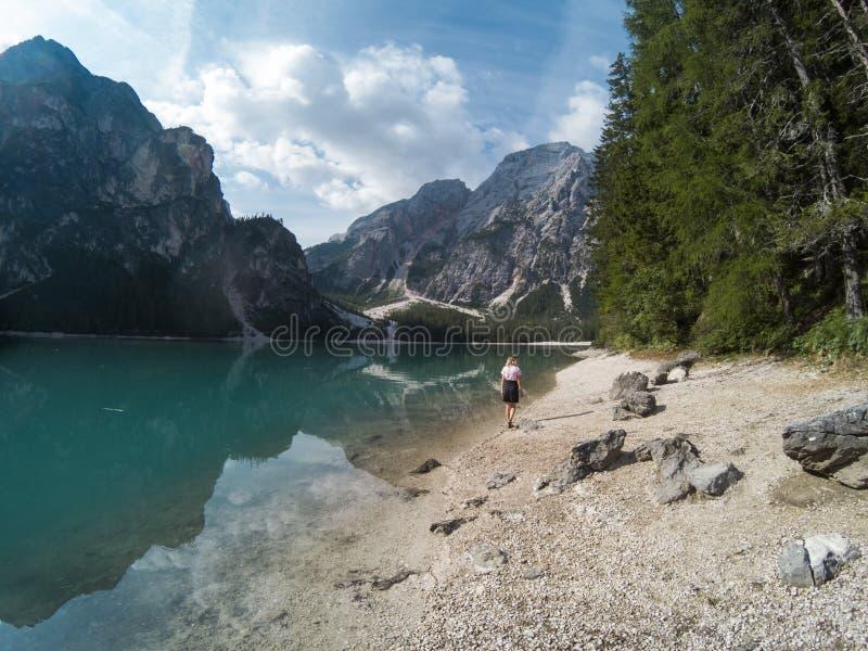 Ragazze che camminano contro la vista stupefacente del lago Braies Lago di Braies con la foresta dell'estate e montagne ha rifles fotografia stock
