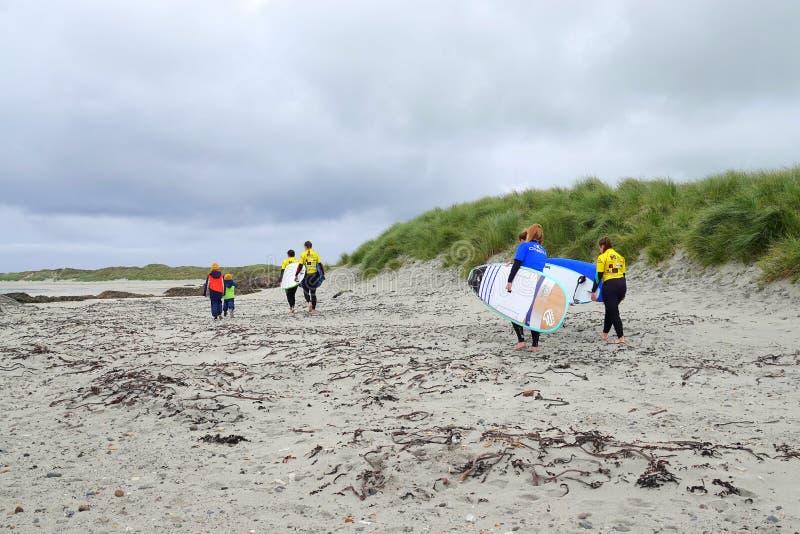 Ragazze che camminano sulla spiaggia con i bordi di spuma fotografia stock