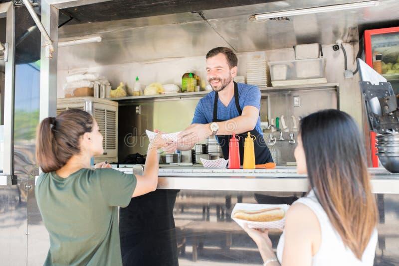 Ragazze che comprano i hot dog dal camion dell'alimento immagini stock