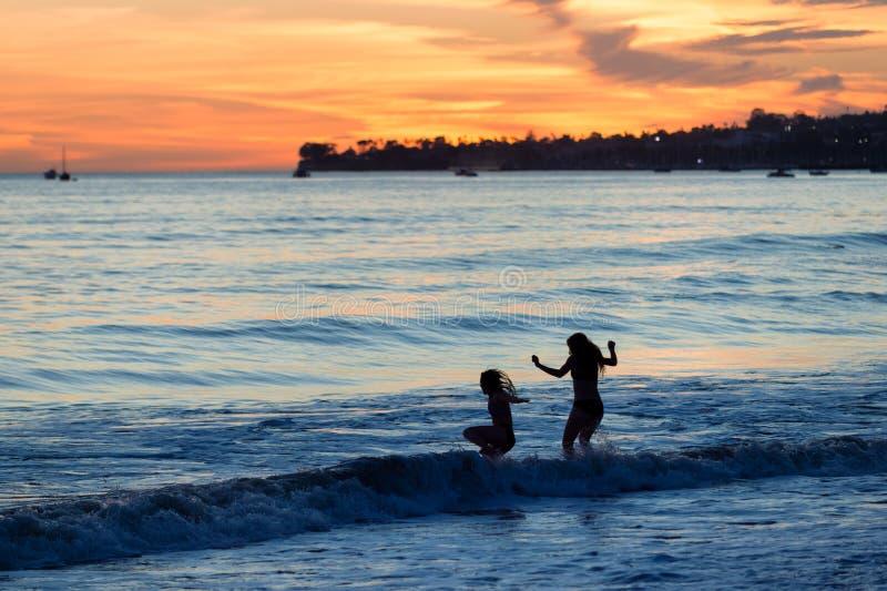 Ragazze che giocano in spuma dell'oceano alla spiaggia immagini stock libere da diritti