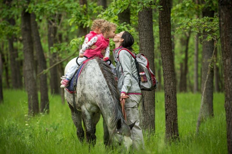 Ragazze che godono dell'equitazione nel legno con la madre, giovani ragazze graziose con capelli ricci biondi su un cavallo, libe fotografie stock