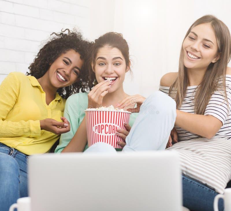 Ragazze che guardano film della commedia e che mangiano popcorn a casa immagini stock libere da diritti