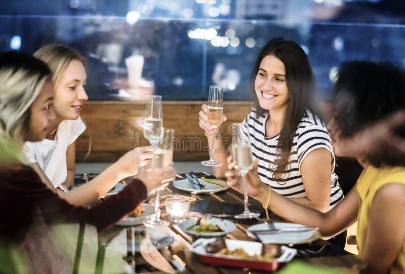 Ragazze che hanno una cena insieme ad una barra del tetto fotografie stock