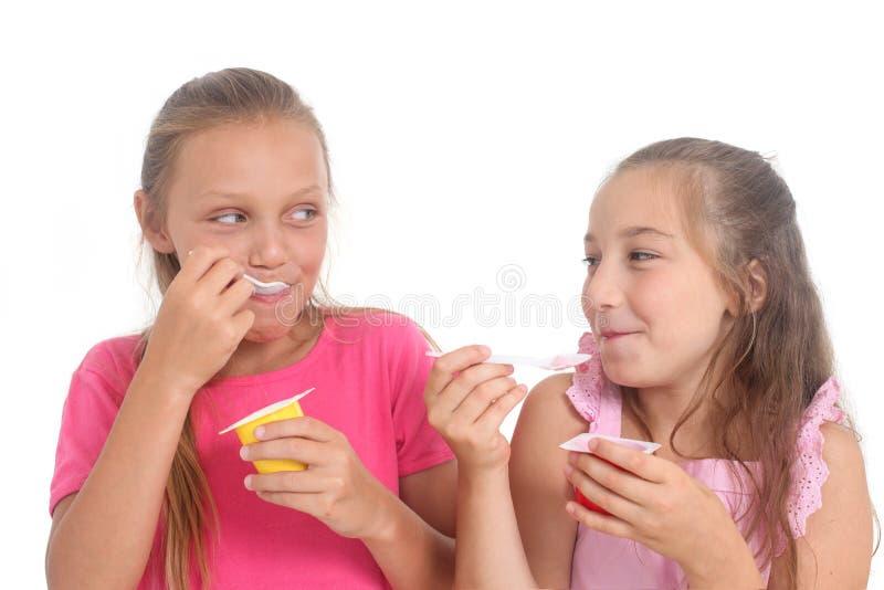 Ragazze che mangiano yogurt fotografia stock