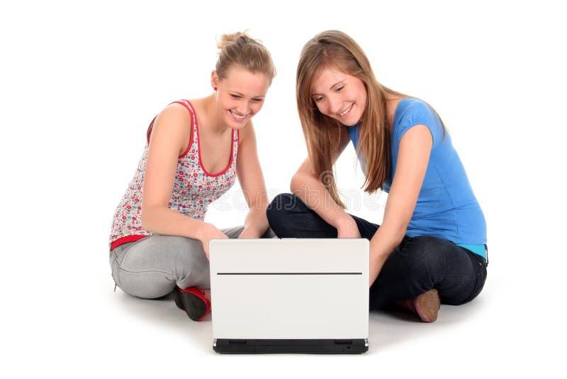 Ragazze che per mezzo del computer portatile immagine stock