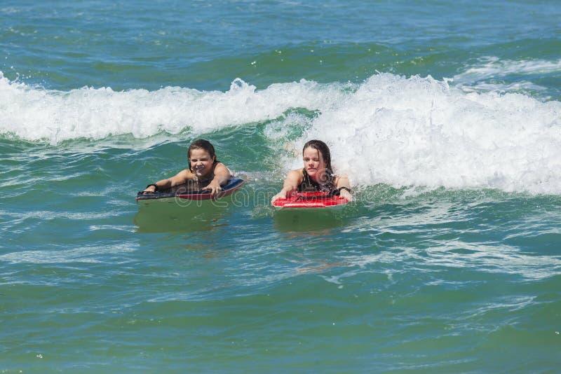 Ragazze che praticano il surfing le onde di oceano fotografia stock libera da diritti