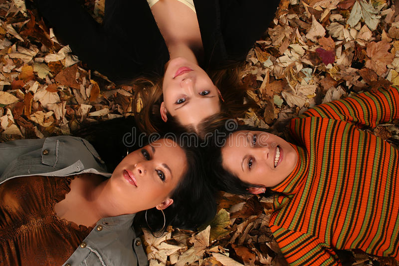Ragazze che risiedono nelle foglie di autunno fotografia stock libera da diritti