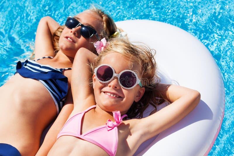 Ragazze che si rilassano sul materasso di nuoto nello stagno fotografia stock libera da diritti