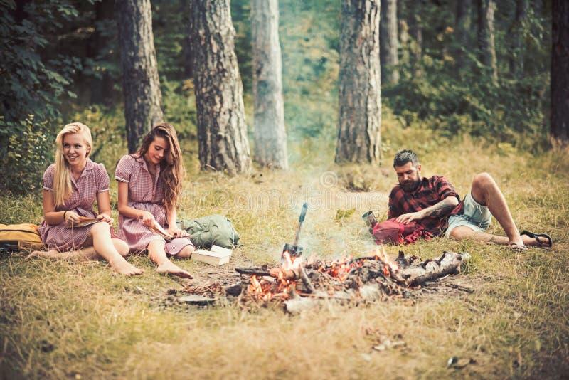Ragazze che si siedono accanto al fuoco di accampamento mentre libri di lettura Tipo barbuto che si trova sull'erba negli amici d fotografia stock libera da diritti