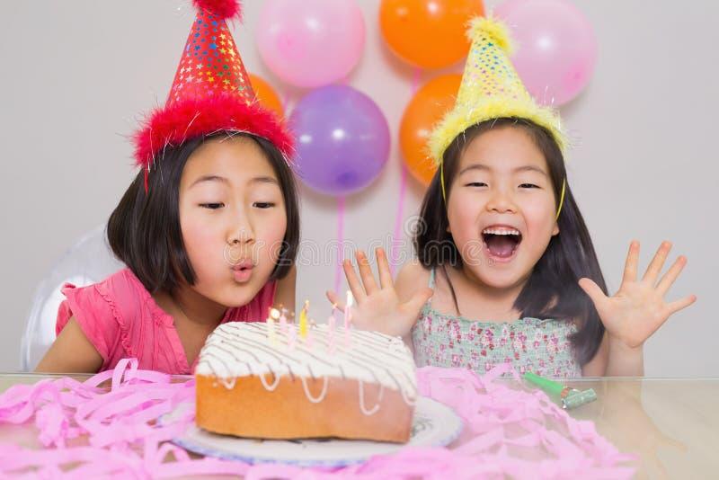 Ragazze che soffiano dolce ad una parte di compleanno immagini stock libere da diritti