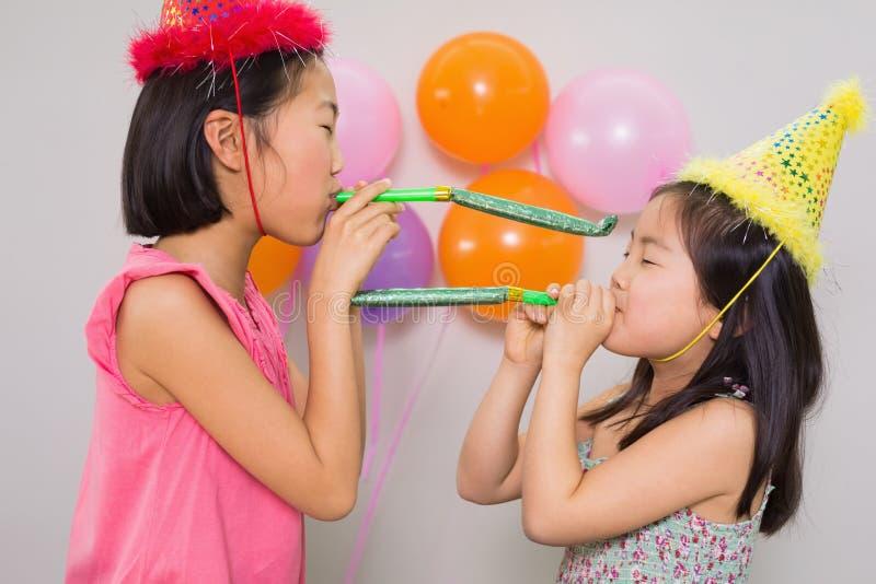 Ragazze che soffiano i noisemakers ad una festa di compleanno fotografia stock libera da diritti