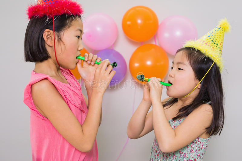 Ragazze che soffiano i noisemakers ad una festa di compleanno fotografie stock