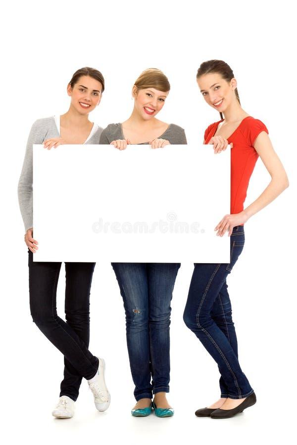 Ragazze che tengono segno in bianco fotografie stock libere da diritti