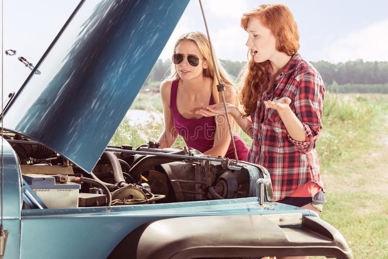 Ragazze che trovano ripartizione dell'automobile fotografia stock libera da diritti