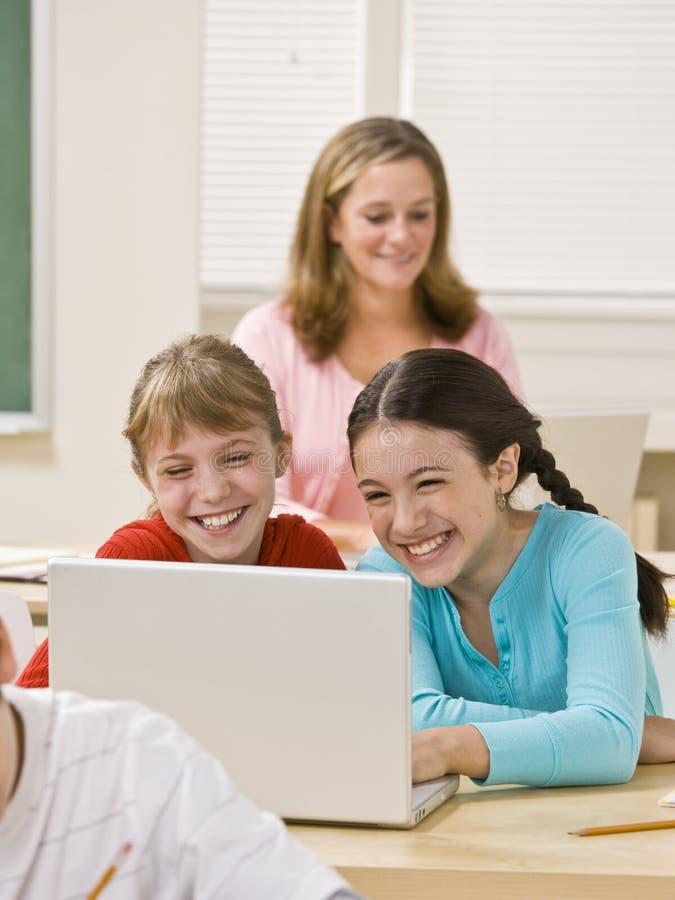 Ragazze che utilizzano computer portatile nell'aula immagine stock libera da diritti