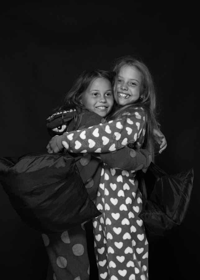 Ragazze con i fronti felici che abbracciano strettamente Amici divertendosi nella lotta di cuscino Partito dei PJs per i bambini: immagini stock