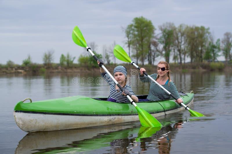Ragazze con i remi nella barca La mamma e la figlia stanno galleggiando in una barca fotografia stock
