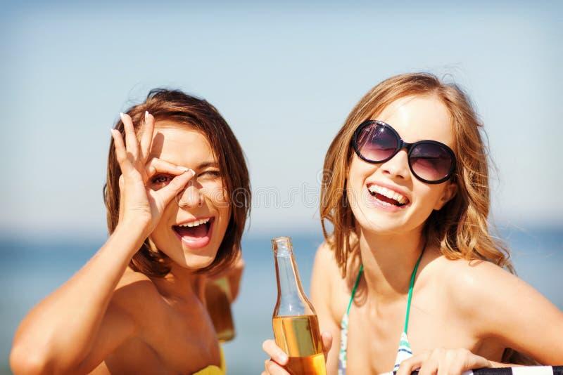 Ragazze con le bevande sulle sedie di spiaggia immagine stock