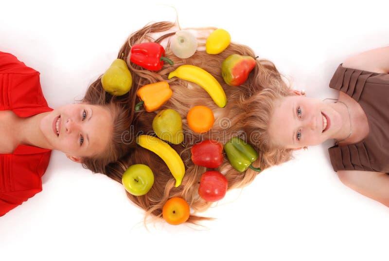 Ragazze del ritratto due con i capelli intrecciati ed i frutti fotografia stock libera da diritti